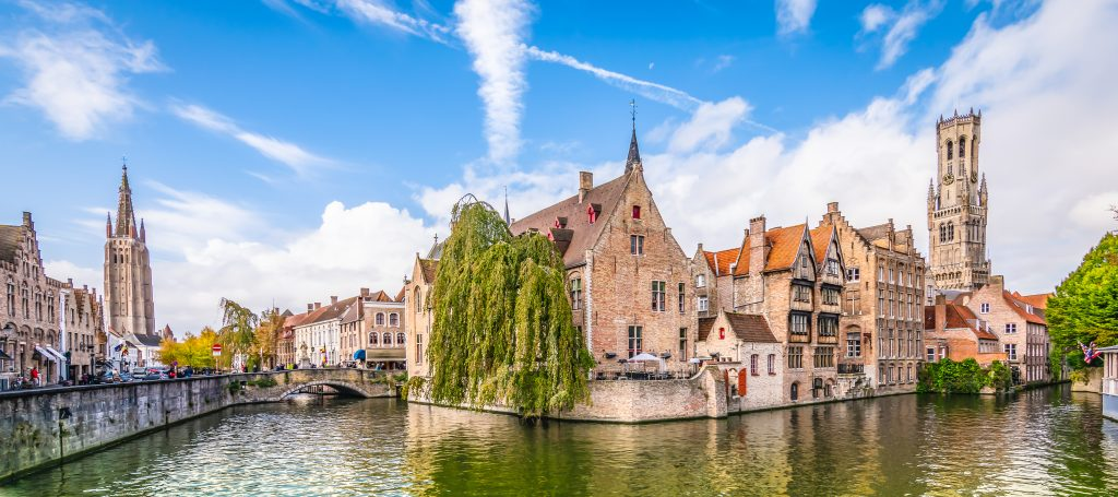 Panoramic city view with Belfry tower and famous canal in Basilica of the Holy Blood in Bruges