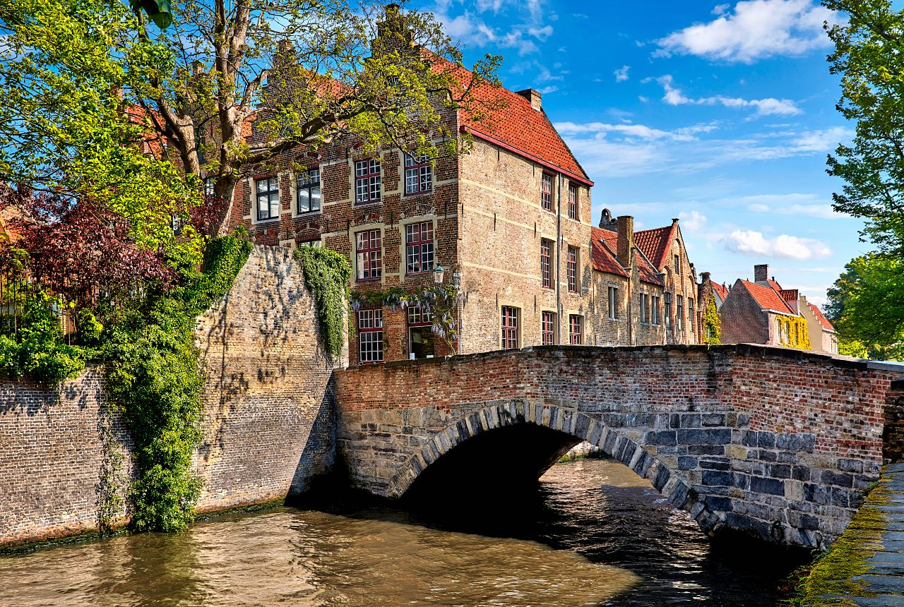 Bruges Belgium vintage stone houses and bridge over canal ancient medieval street